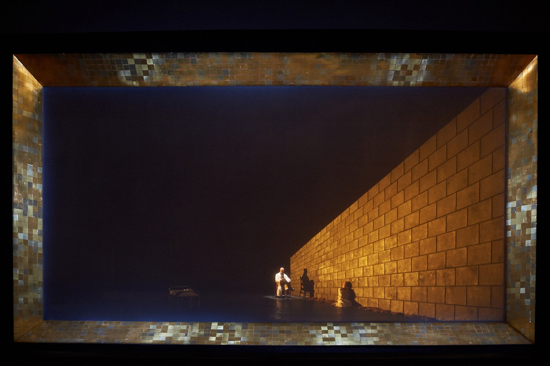 Gold tiles frame warm-lit angled wall with knelling woman in straight-jacket and doctor seated behind.