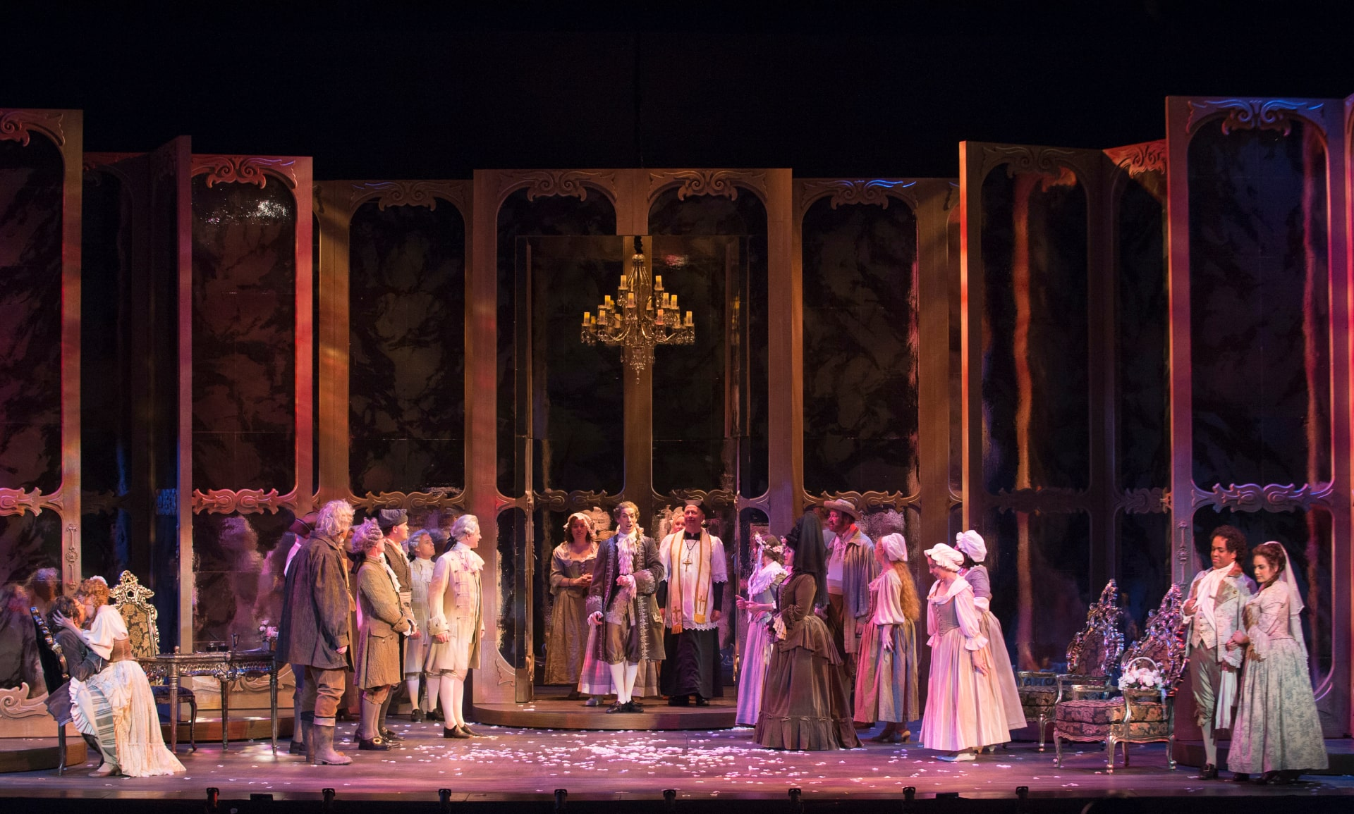 Opera players in 18th century attire scattered under lavender in front of towering, painted revolving doors.