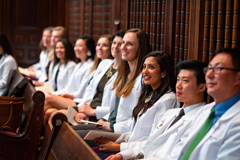 Students smiling and sitting at the white coat ceremony at medical school graduation