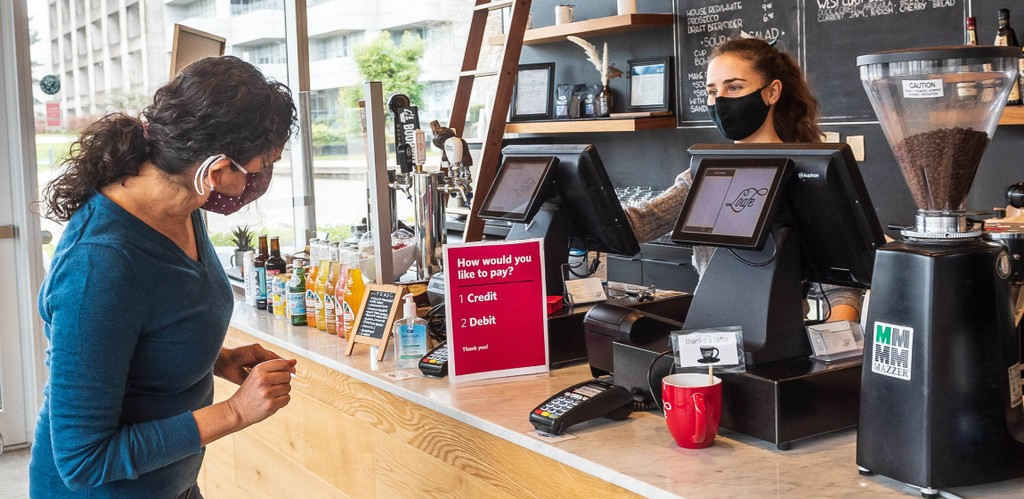 A patron wearing a COVID-19 masks tries to pay for purchase from mask-wearing cashier at a coffee shop