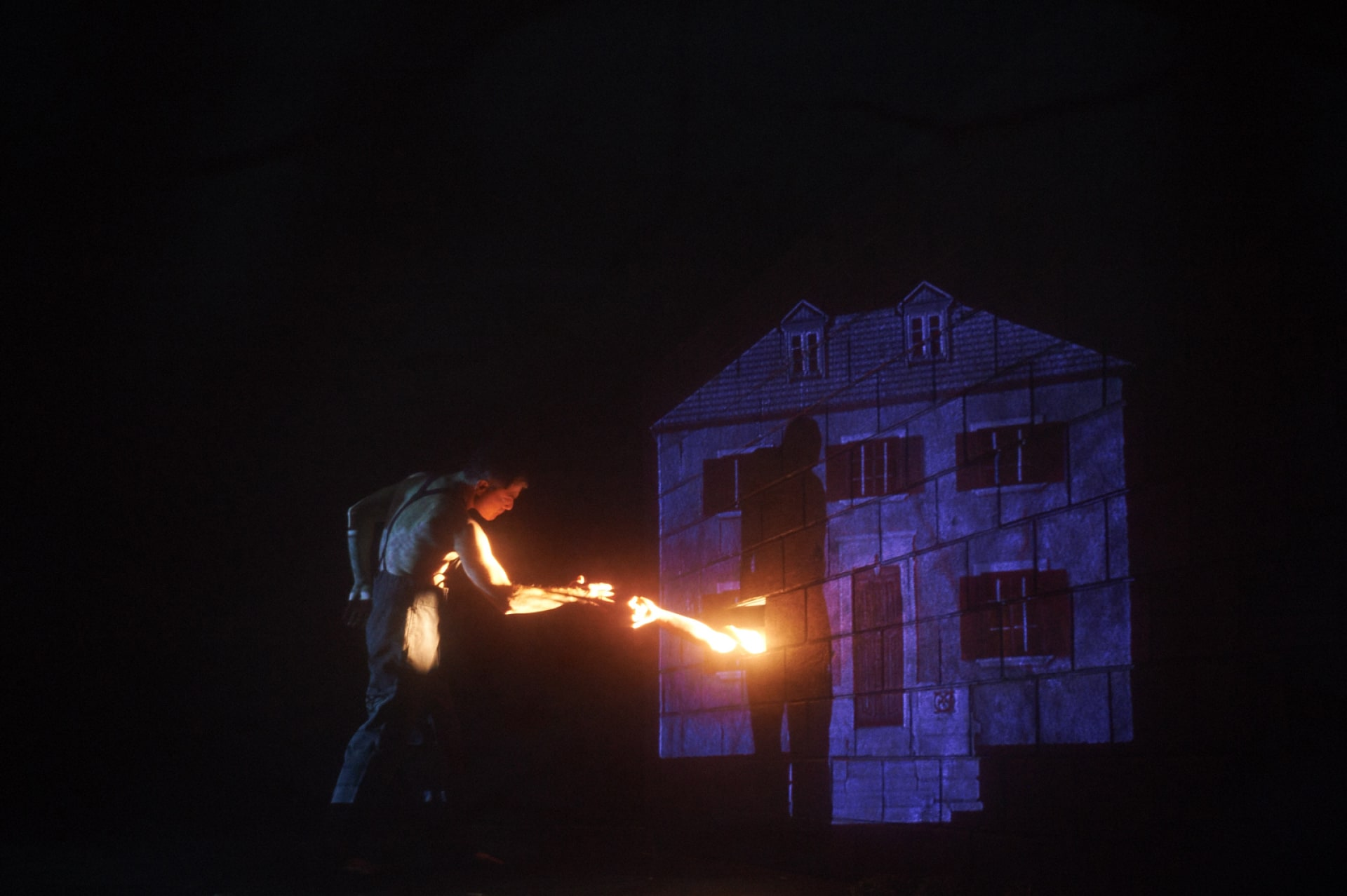 Shirtless man in suspenders reaches to brightly lit arm emerging from projected cottage.
