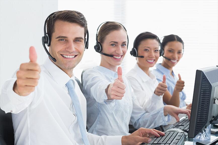Plusieurs employés d'un centre d'appel sourient et lèvent le pouce