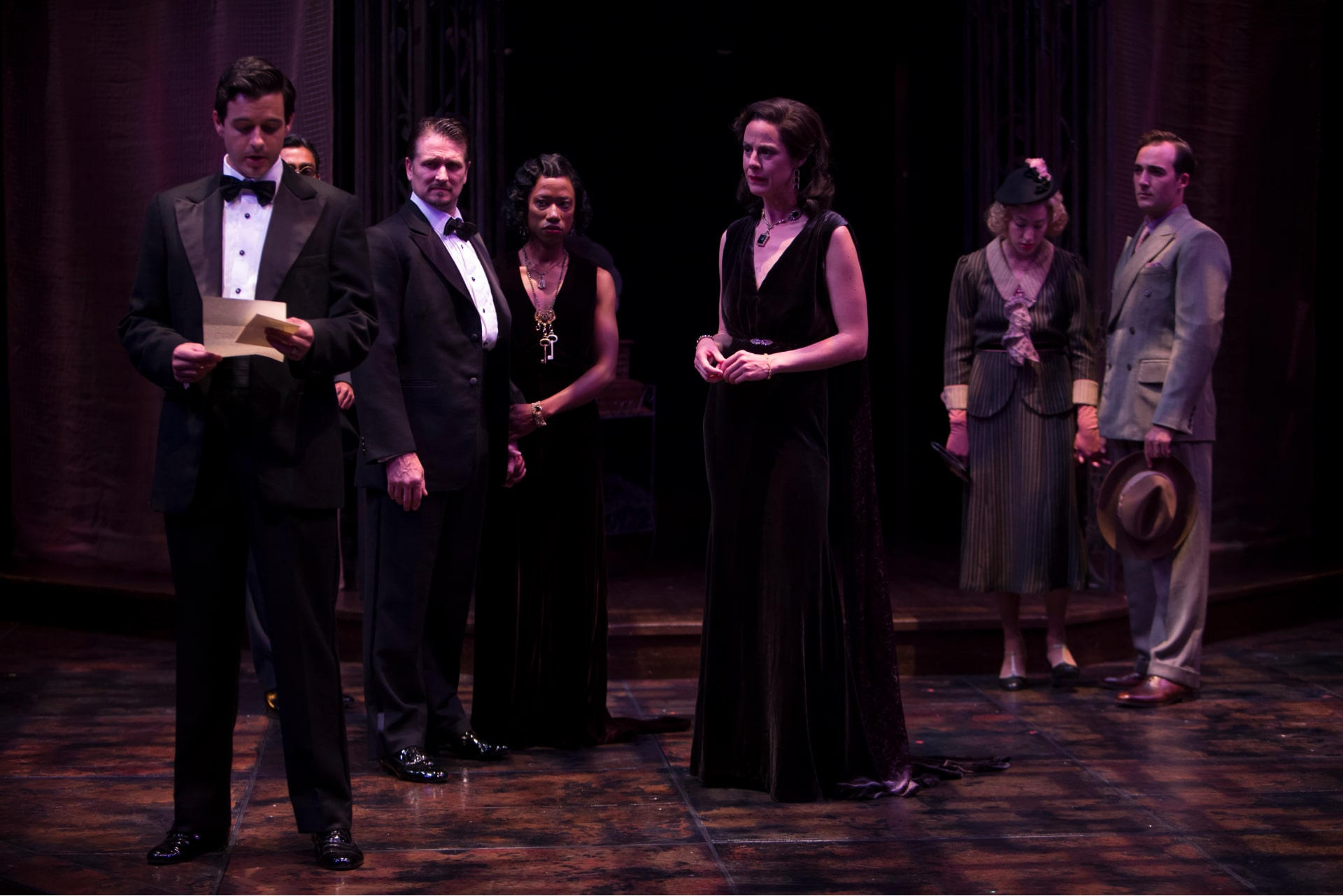 Man in dinner jacket reads letter to woman in black gown and others under dappled lavender light on bare stage.