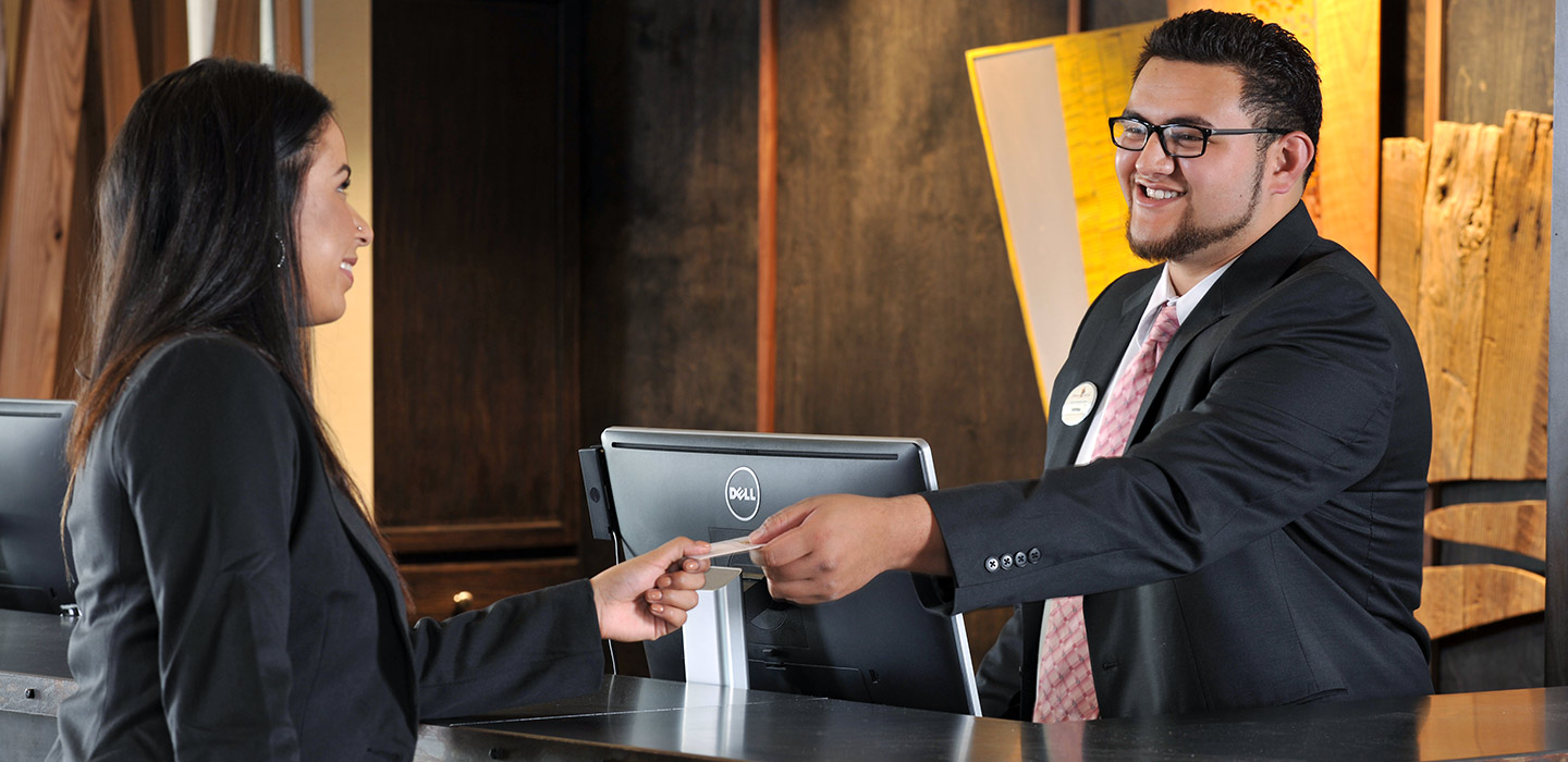 Front desk agent presenting key to guest