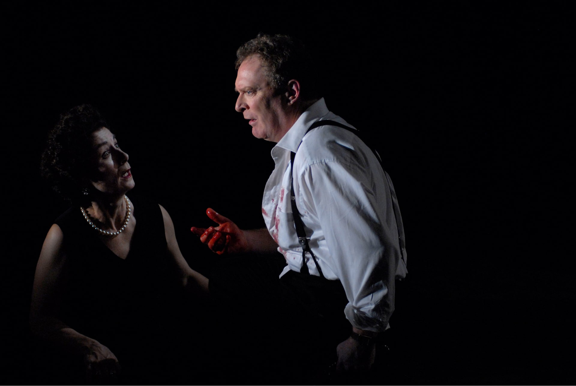 Woman in sleeveless black dress and pears stares at man in shirt-sleeves with bloody hand.