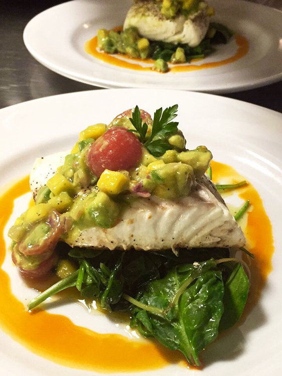 Chef's Special Halibut topped with avocado mango relish on a bed of sauteed spinach surrounded by chili oil - A dish from our daily fresh fish rotation