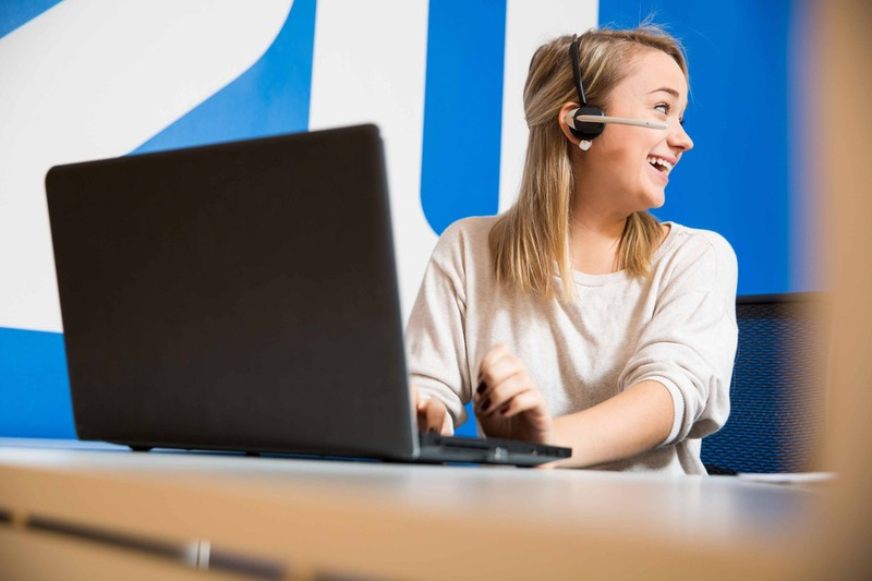 Woman laughing on a wireless headset and typing on a laptop in front of a blue wall with the 2U logo on it