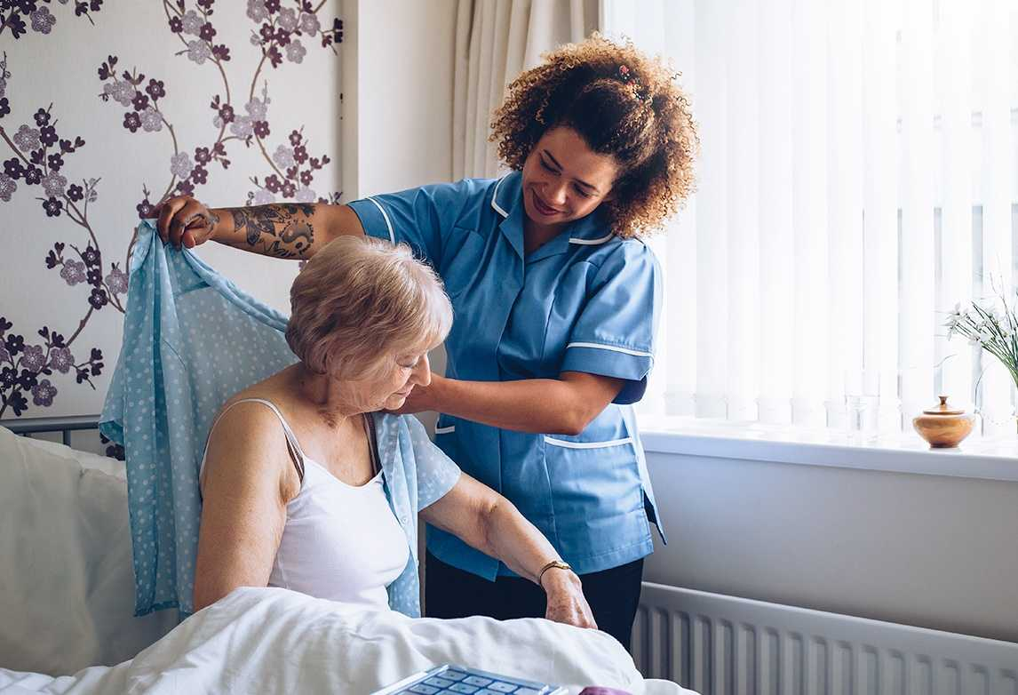 A patient care technician assists an elderly woman, helping her to get dressed.