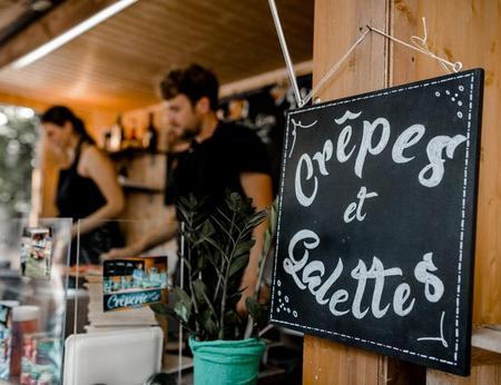 Crepe- und Galettezubereitung in mobilem Creperie Food Truck hinter einem schön beschriebenen Crepes und Galettes Schild