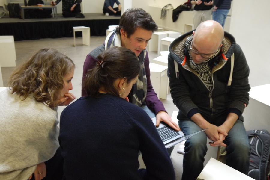 Quatre personnes sont assises et discutent, penchées autour d'un écran d'ordinateur