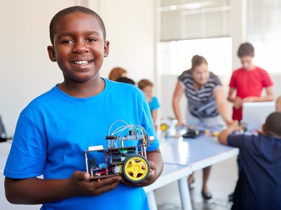 A young student holds a machine that he made.
