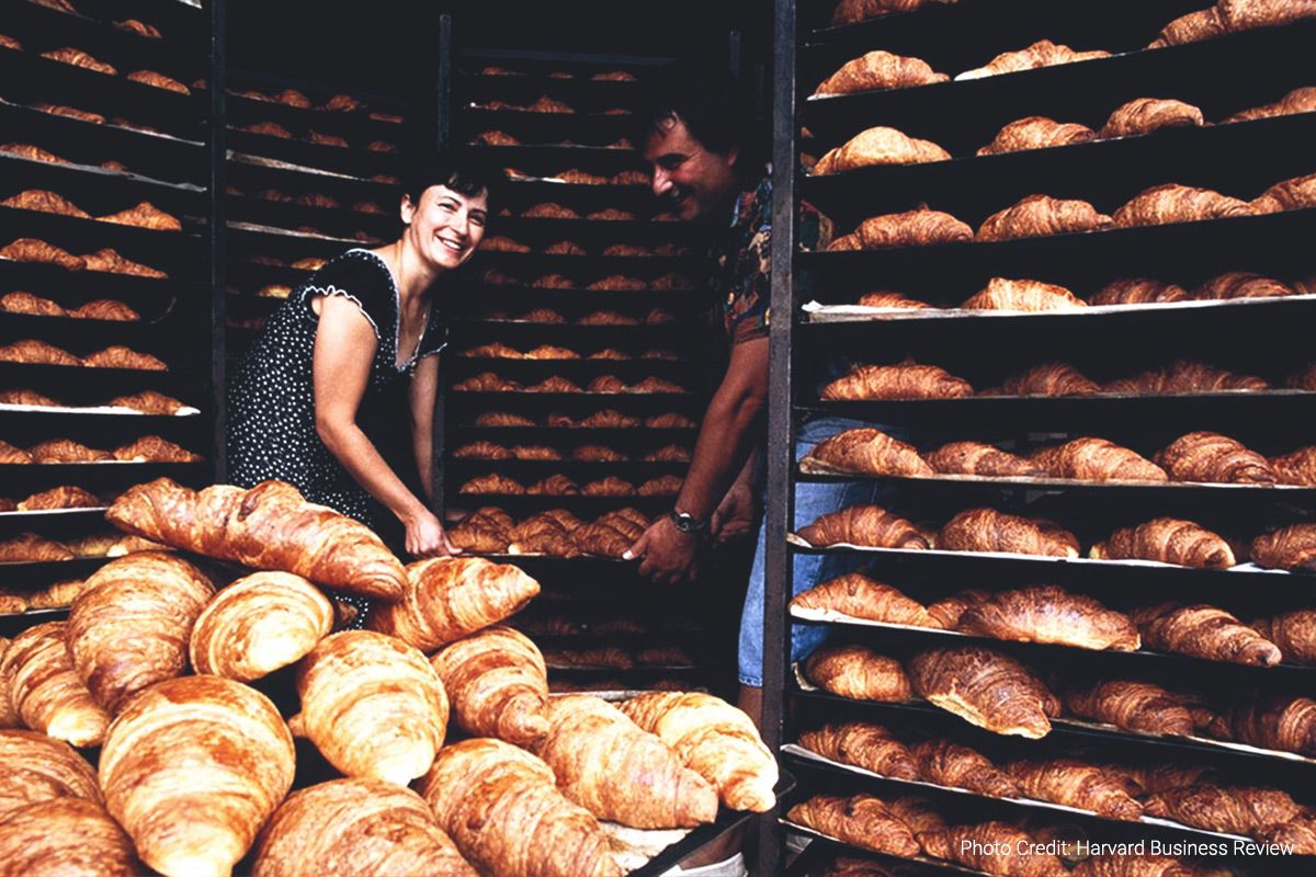a woman and a man hold a tray while surrounded by racks and racks full of fresh-baked croissants (photo credit: harvard business review)