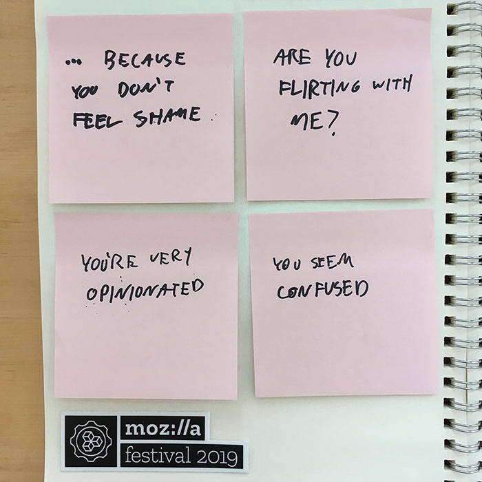 pink sticky notes in a grid of four pasted into a notebook