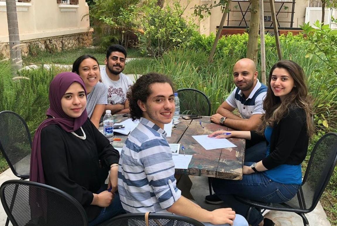 Mosaik team around a table in a garden