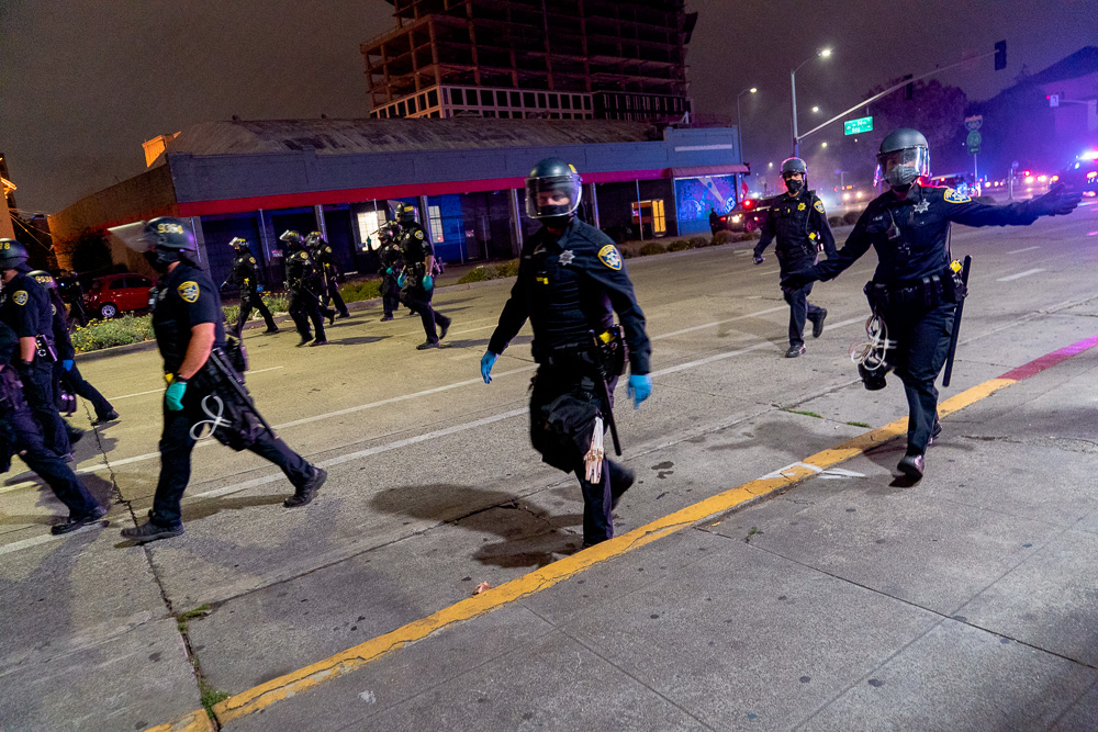 Oakland Police Department officers follow the 'Justice for Jacob' protest down Harrison Street in Oakland, Calif., August 26, 2020. Shortly after police declared the protest an unlawful assembly and gave people five minutes to disperse.