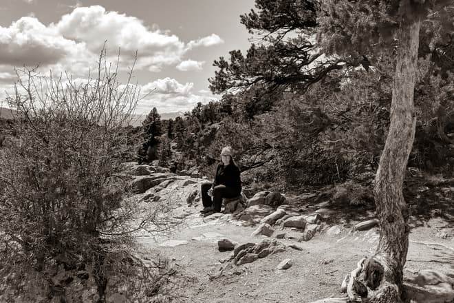 A black-and-white photograph of Len sitting on a rock just outside of a pine and juniper forest.