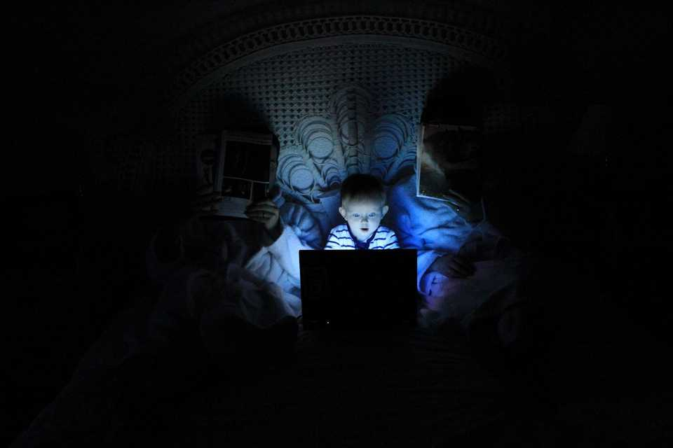 Child playing with laptop on bed