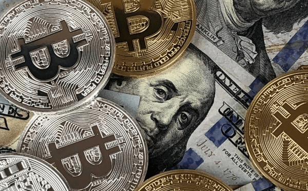 Some Bitcoins laying on a Dollar bill.
