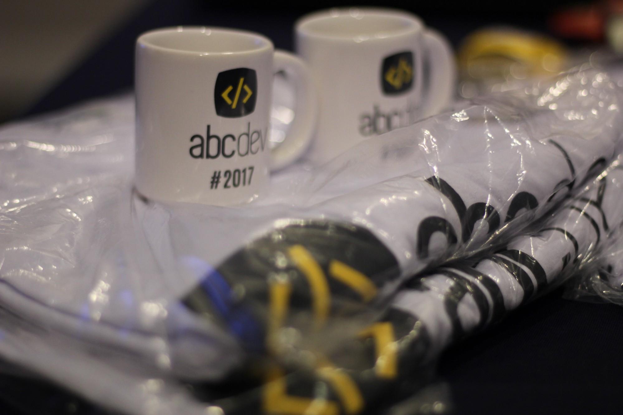 Imagem dos brindes do ABC-Dev 2017, camisetas e canecas