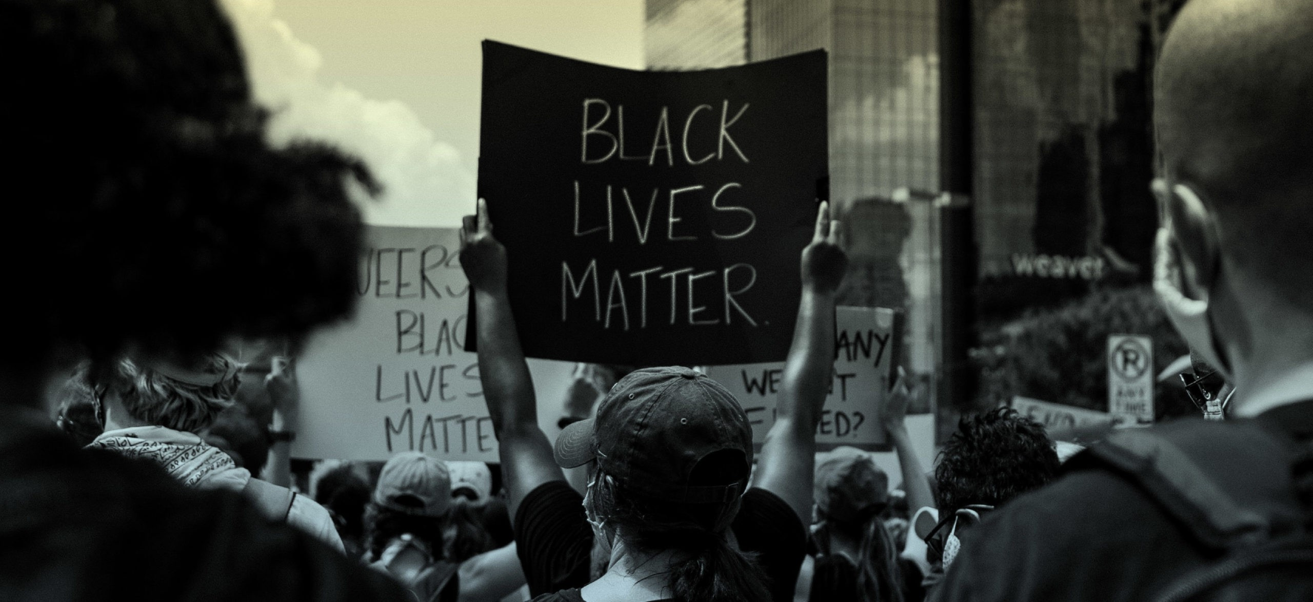 A group of people holds anti-racist signs at a Black Lives Matter protest