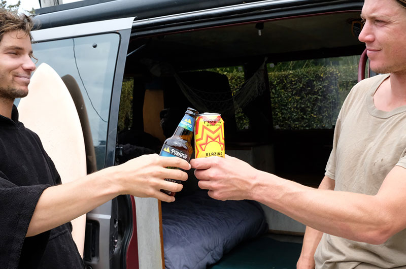 A man holding a bottle of Outburst cheering a man holding a can of Blazing Bright outside of a van