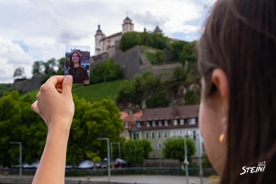 Hier hält jemand sein gerade erhaltenes Foto in der Hand und betrachtet es. Aufgenommen auf der Alten Mainbrücke in Würzburg.