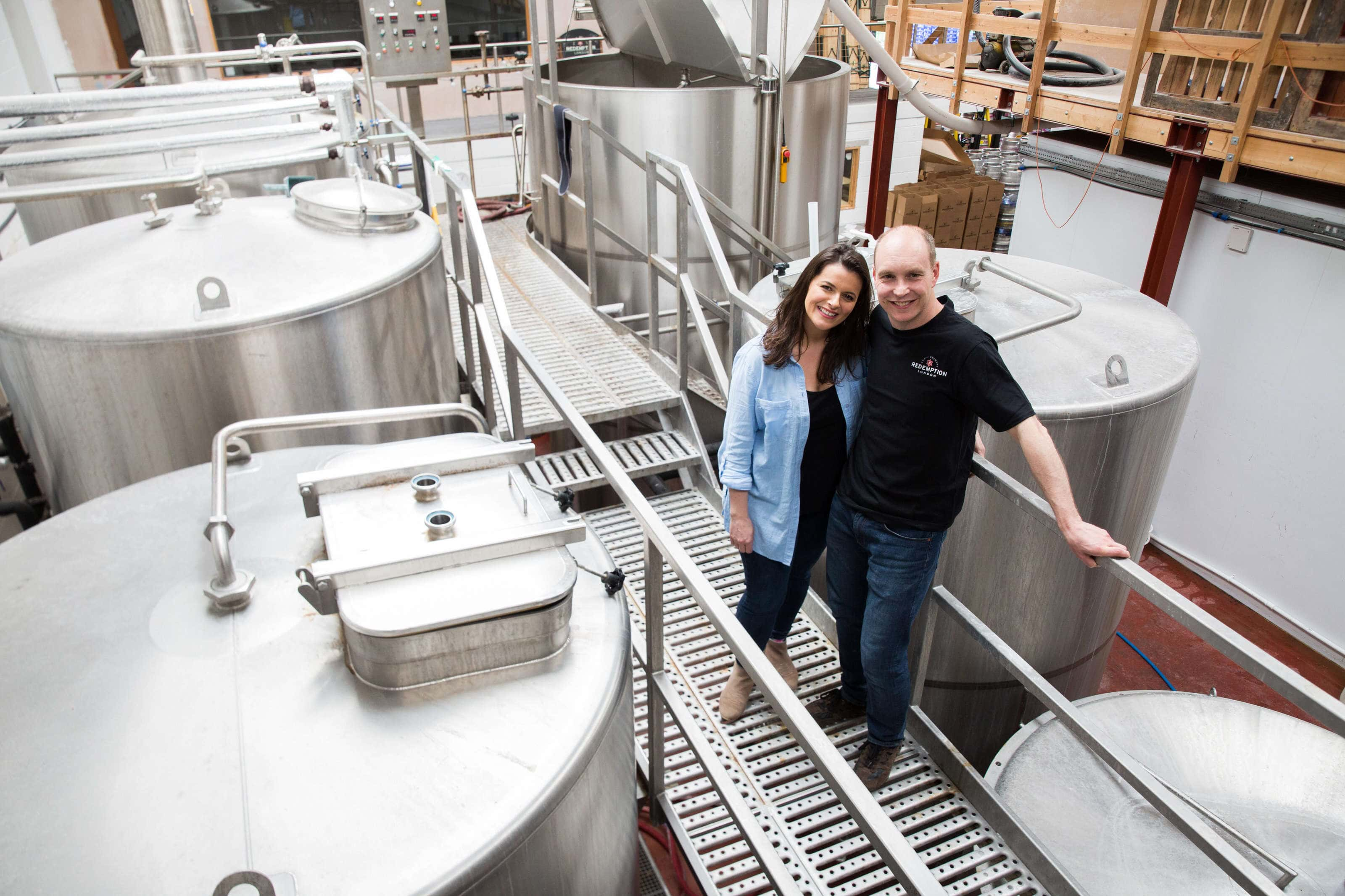 Portrait of Andy and Sam Rigby the owners or redemption brewery stood on the walk way above the beer vats in the brewery.