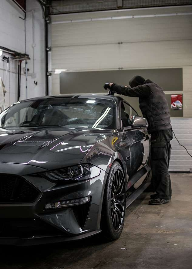 Man in gloves polishing Grey Mustang GT with machine