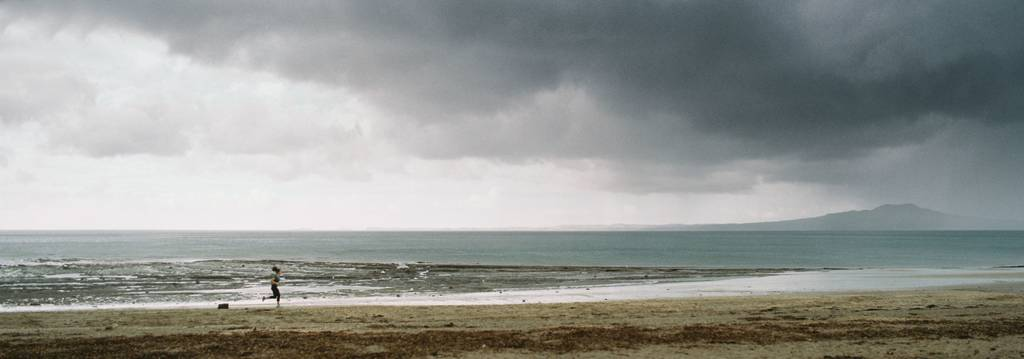 Panorama of a woman running up the beach with a cloudy mountain in the background