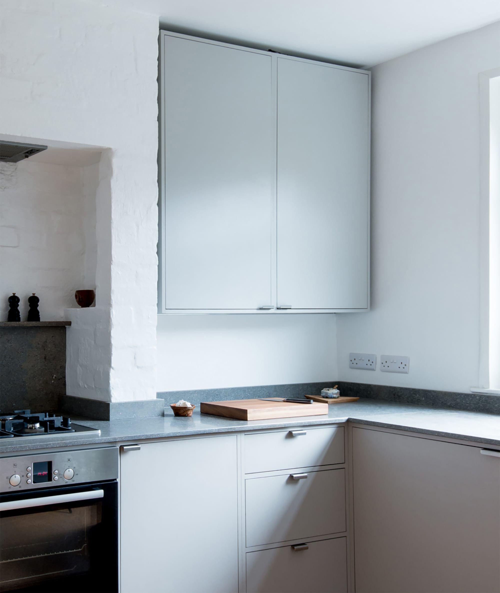 Tall grey kitchen wall units with dark grey limestone worktop.
