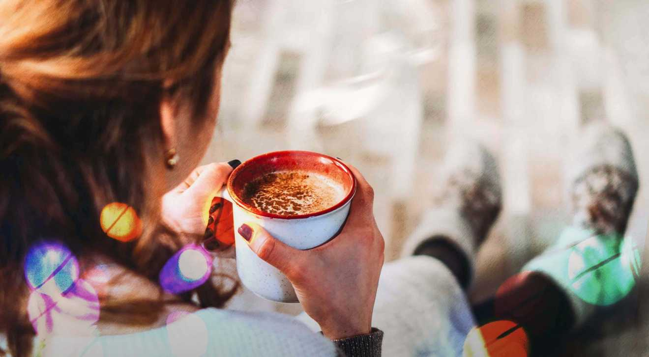 A women drinks hot chocolate to improve her mental health over the holiday season