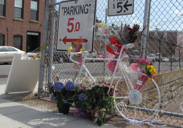 "A ""ghost bike"" memorial in Sullivan Square where a 30-year old was struck and killed by a garbage truck, which then fled the scene."