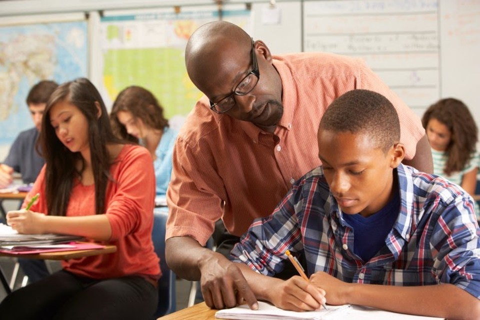 African American teacher in high school classroom looks over the shoulder of one of his students, an African American teenage boy, and points to his notebook.