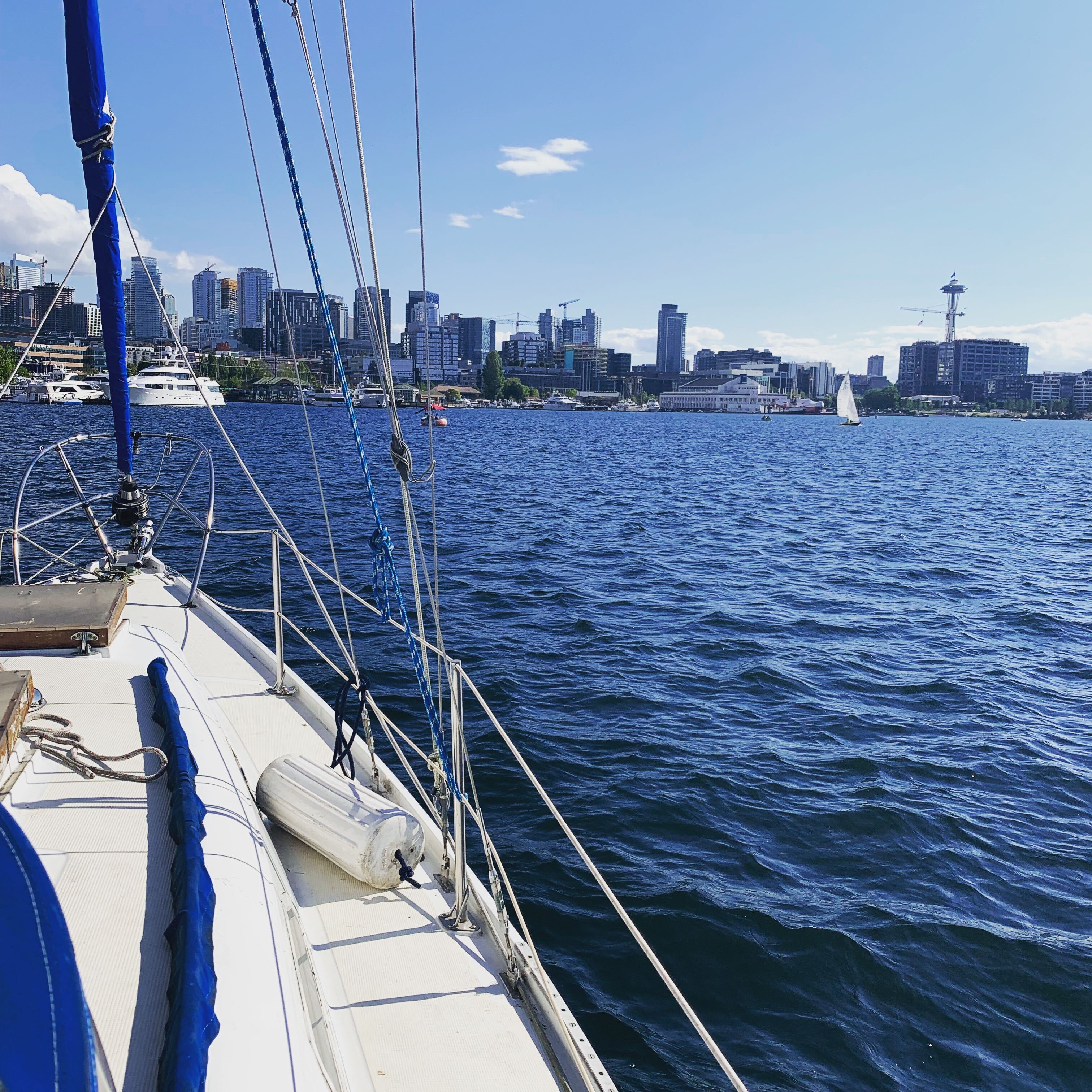 A picture of downtown seattle, the space-needle, with a bow of a sailboat in the foreground,