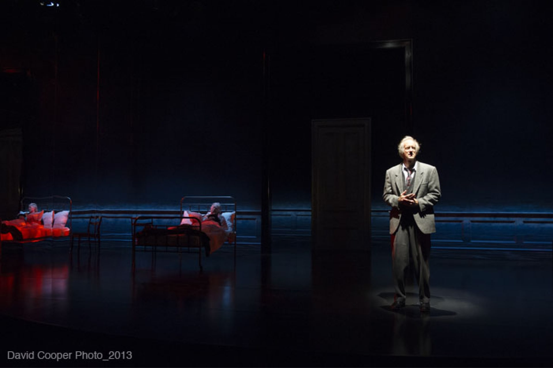 Man in grey suit stands in pool of light while woman in red-lit bed is reflected in mirror wall behind.