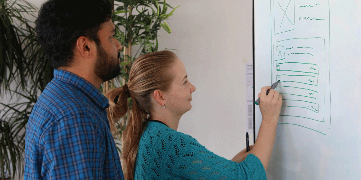 A man and a woman UX designer smiling and  wireframing using a whiteboard