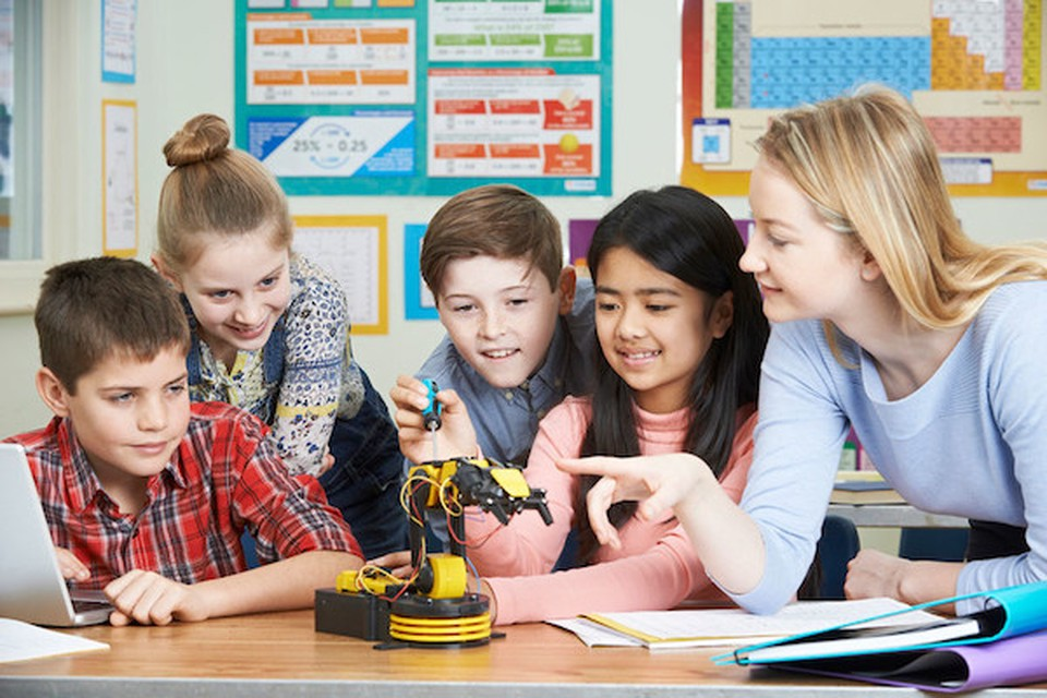 A woman pointing at a small robot. Four children are smiling and looking at the robot.
