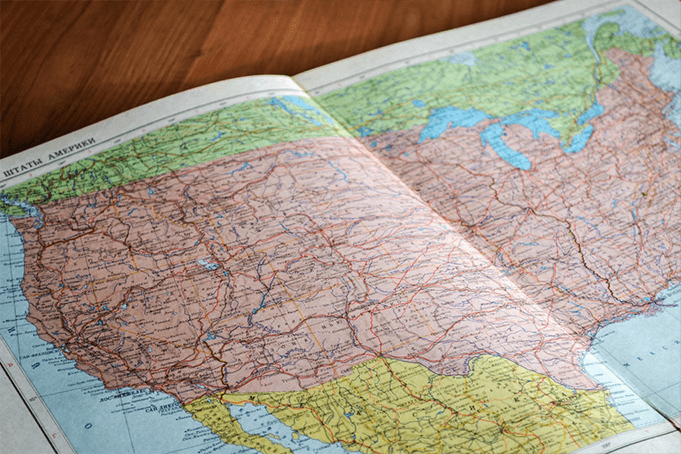 A road atlas spread out on a table of the United States
