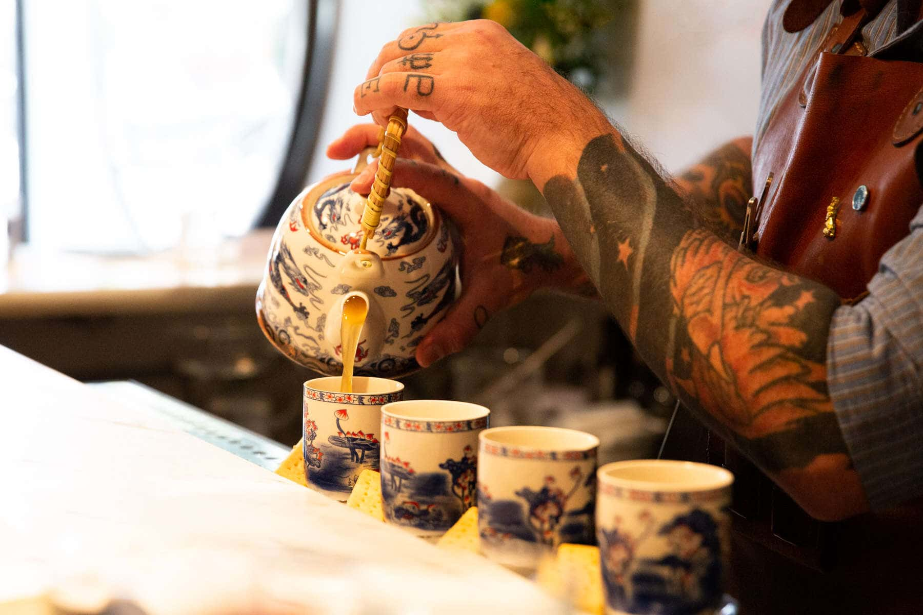 tea cocktail being pored by tattooed bartender