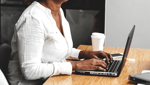 A woman in a white shirt typing at a laptop moving into the advisory space with a coffee cup next to her on a desk.