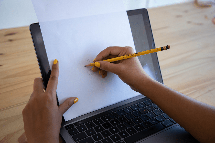 during an icebreaker, a woman draws a shape with a pencil on a piece of paper placed on top of her laptop screen