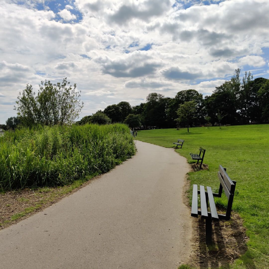 Large path leading around the edge of Yeadon Tarn lake with benches and green grass to the right