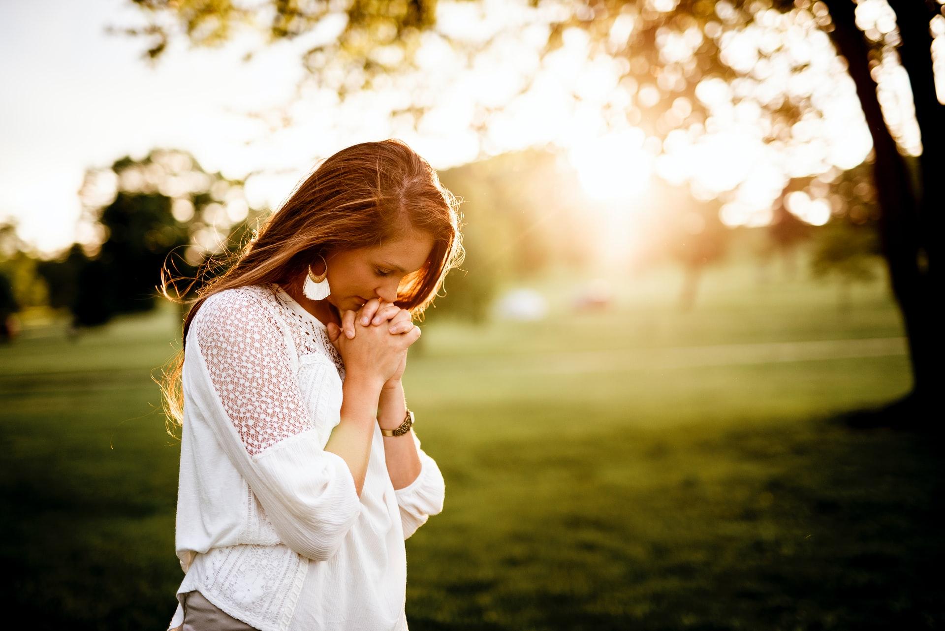 Mulher orando no nascer do Sol