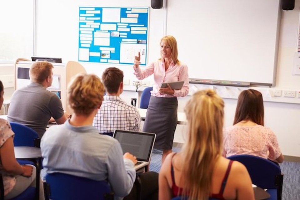A woman teaching a classroom full of adults