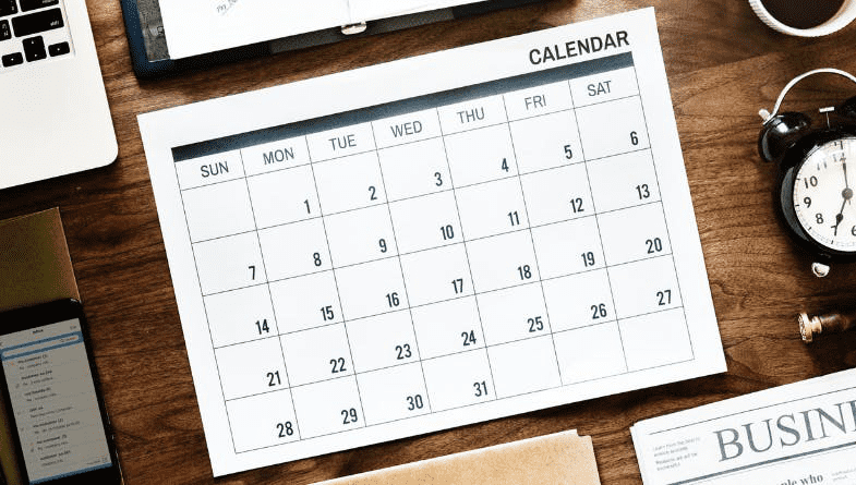 Calender on wooden desk surrounded by notepad and phone, clock, file, newspaper and plant to be used for 7 seven productivity tools for accountants to be more productive in accountancy list by Futrli #productivity