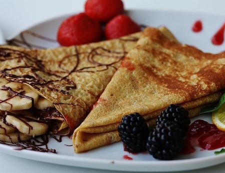 Mit Erdbeeren, anderen Früchten und Schokosauce verzierte süße Crepes