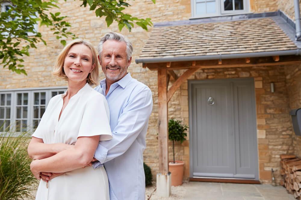 Glückliches Paar vor verrenteter Immobilie