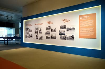 A wall featuring photos of city areas, that were taken by Lee Kip Lin.
