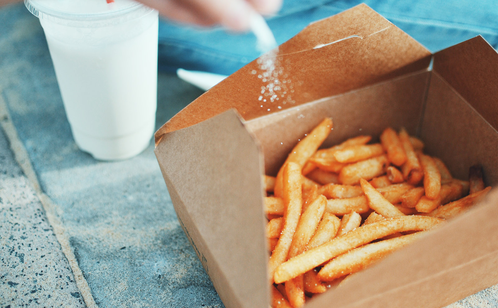 basket of french fries being sprinkled with salt