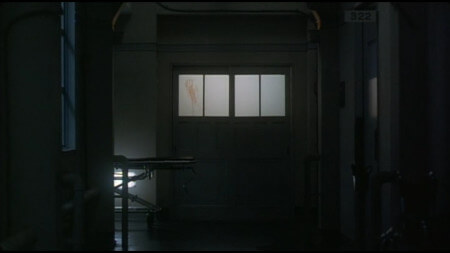 An ominous shot of a hospital corridor, with a set of double doors in the centre of the frame. The double doors have windows at about shoulder height, and one of the windows has a bloodied handprint smeared down it
